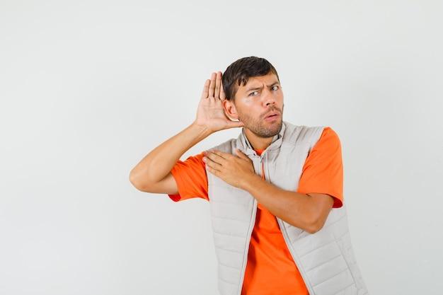 Junger mann, der hand hinter ohr hält, während er im t-shirt, in der jacke mithört und neugierig schaut. vorderansicht.