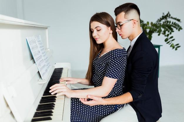 Junger mann, der hand ihrer freundin für das spielen des klaviers hält