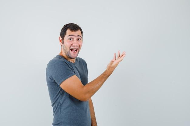 Junger mann, der hand im grauen t-shirt erhebt und glücklich schaut