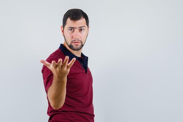 Junger mann, der hand in der fragenden geste im t-shirt erhebt und ernst schaut. vorderansicht.