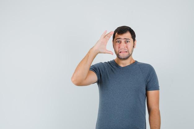 Junger mann, der hand nahe kopf im grauen t-shirt hält und traurig schaut