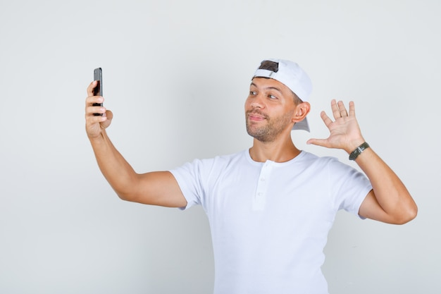 Junger mann, der hand wendet, während videoanruf im weißen t-shirt, mütze und glücklich schauende vorderansicht hat.