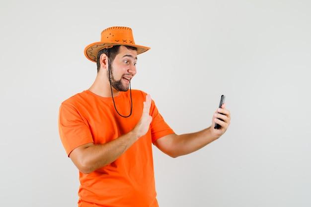 Junger mann, der hand winkt, während er selfie in orange t-shirt, hut nimmt und fröhlich schaut