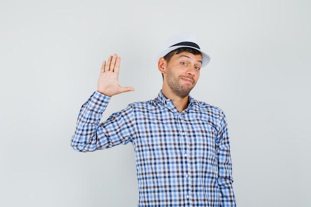 Junger mann, der hand zum begrüßen im karierten hemd winkt