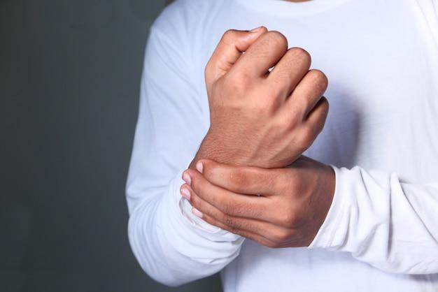 Junger mann, der handgelenksschmerzen leidet, nahaufnahme.