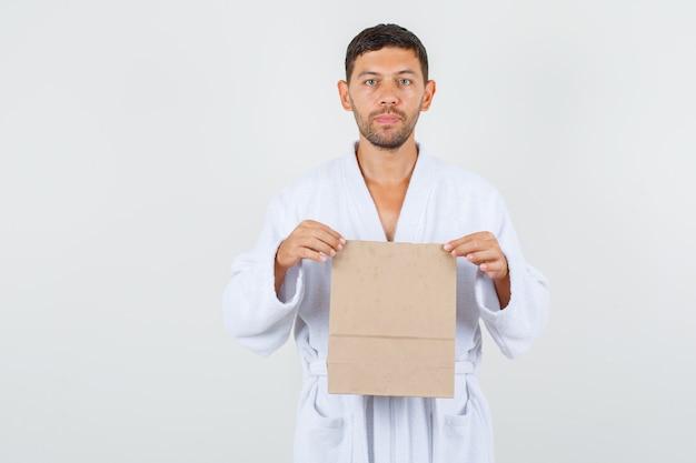 Junger mann, der handwerkspapiertasche im weißen bademantel hält und strenge vorderansicht schaut.