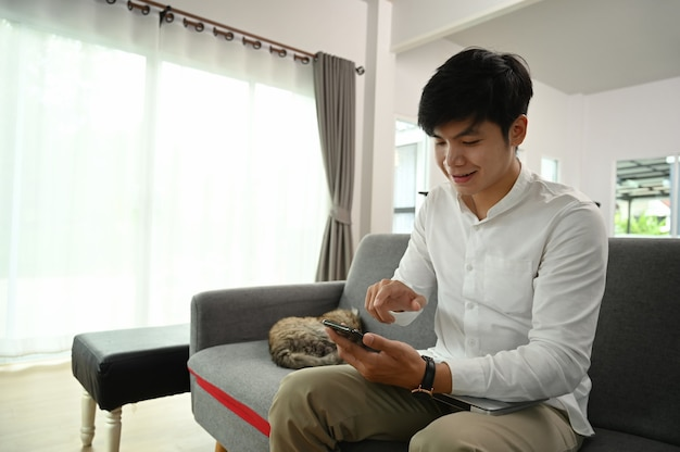 Junger mann, der handy auf couch mit seiner katze im modernen haus benutzt.