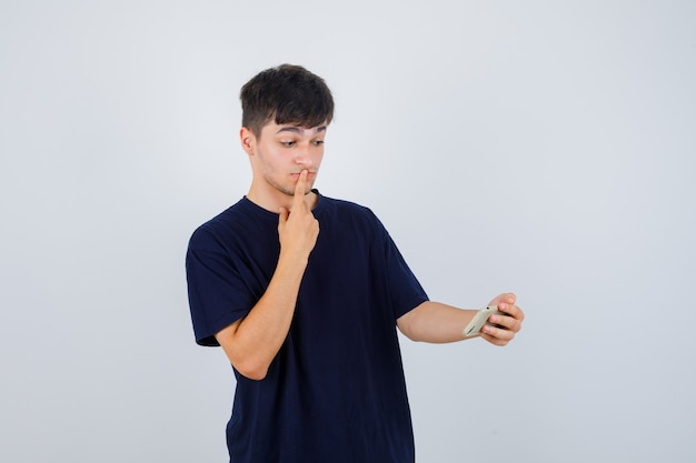 Junger mann, der handy betrachtet, finger auf lippen im schwarzen t-shirt hält und verwirrt, vorderansicht schaut.