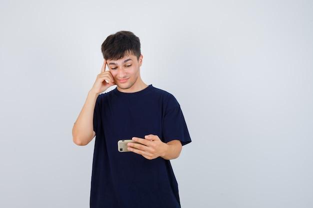Junger mann, der handy betrachtet, hand auf kopf im schwarzen t-shirt hält und nachdenklich, vorderansicht schaut.