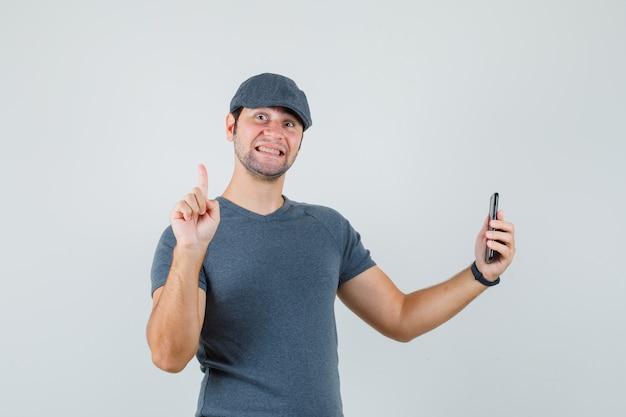 Junger mann, der handy hält, das oben in der t-shirt-kappe zeigt und fröhlich schaut