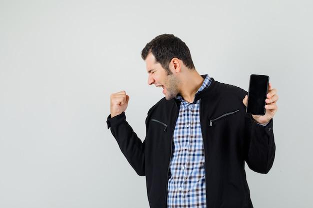 Junger mann, der handy hält und siegergeste in hemd, jacke zeigt und glück schaut.