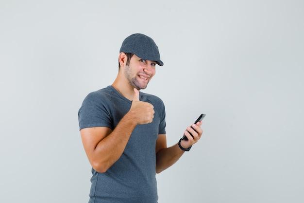 Junger mann, der handy hält, zeigt daumen oben in der t-shirt-kappe und schaut lustig