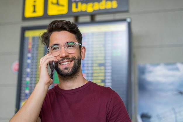 Junger mann, der handy im flughafen spricht