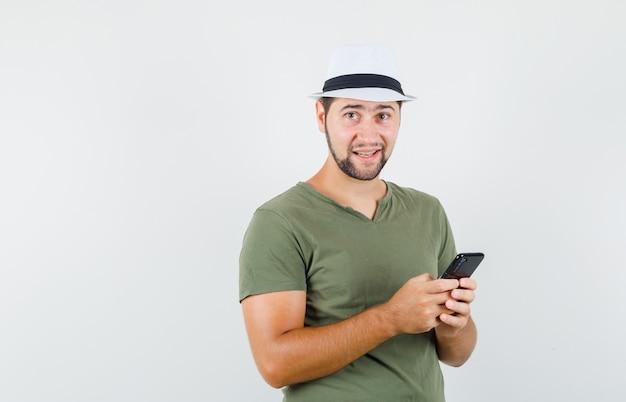 Junger mann, der handy im grünen t-shirt und im hut hält und fröhlich schaut