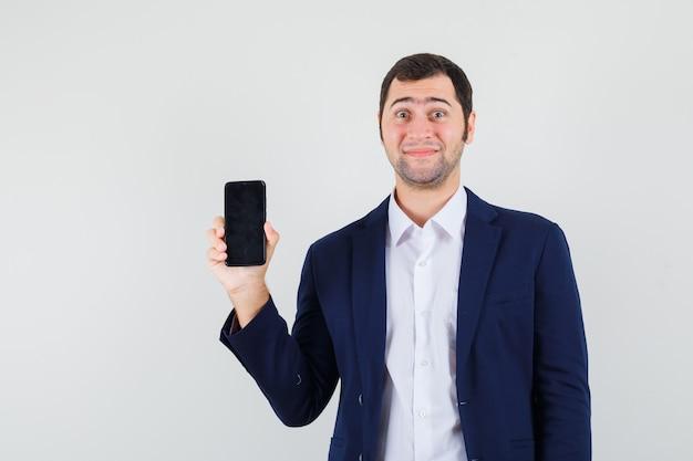 Junger mann, der handy im hemd hält Kostenlose Fotos