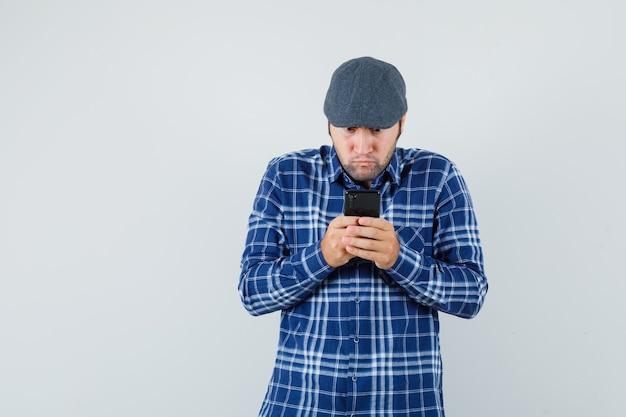 Junger mann, der handy im hemd, in der kappe verwendet und fokussierte vorderansicht schaut.