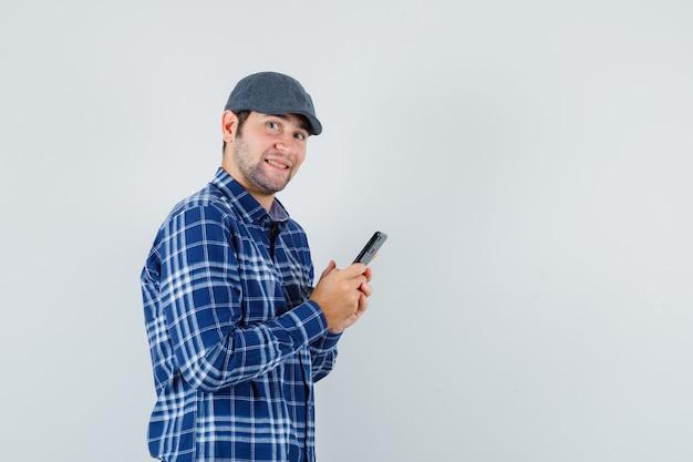 Junger mann, der handy im hemd, in der mütze und in der fröhlichen vorderansicht verwendet.
