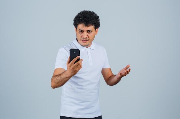 Junger mann, der handy im weißen t-shirt betrachtet und verwirrt schaut, vorderansicht.