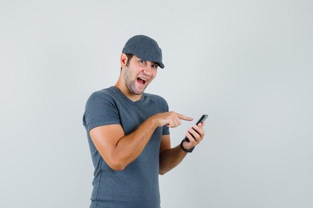 Junger mann, der handy in der t-shirt-kappe benutzt und lustig schaut