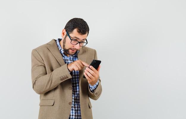 Junger mann, der handy in hemd, jacke benutzt und beschäftigt schaut