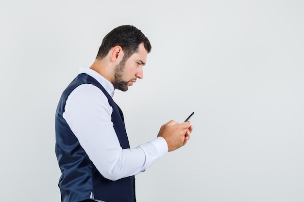 Junger mann, der handy in hemd und weste benutzt und beschäftigt schaut.