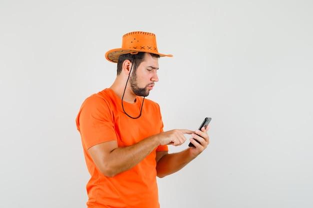 Junger mann, der handy in orange t-shirt, hut und beschäftigt beschäftigt
