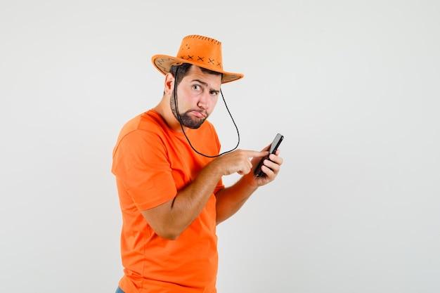 Junger mann, der handy in orange t-shirt, hut und nachdenklich schaut.