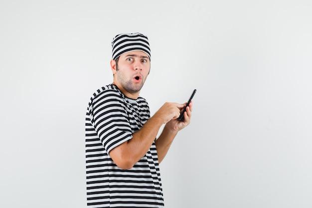 Junger mann, der handy in t-shirt, hut benutzt und überrascht schaut.