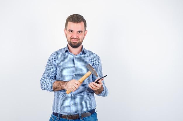 Junger mann, der handy mit einem hammer im hemd, in den jeans schlägt und glücklich schaut. vorderansicht.