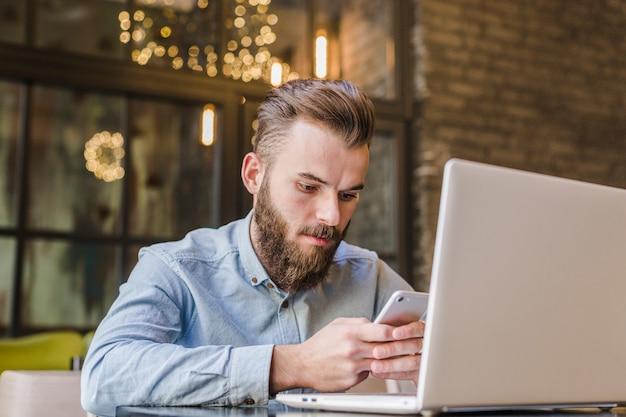 Junger mann, der handy mit laptop auf schreibtisch verwendet