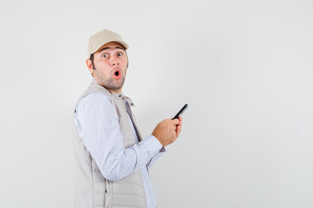 Junger mann, der handy zur hand in beiger jacke und mütze hält und überrascht schaut. vorderansicht.