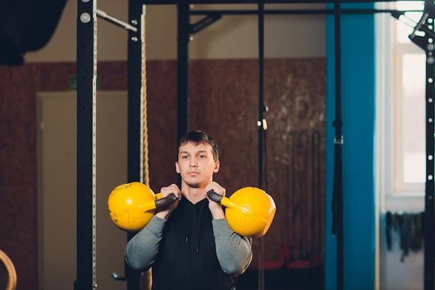 Junger mann, der hantel und kettlebell am fitnesscenter anhebt.