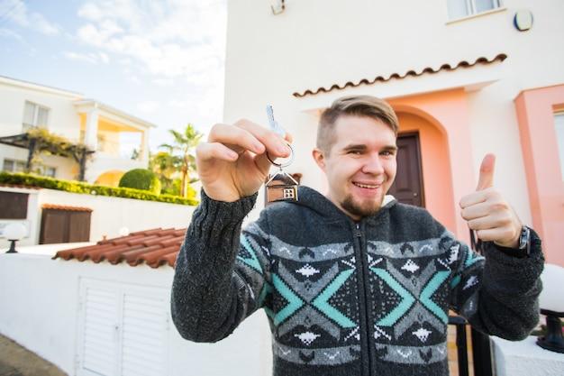 Junger mann, der hausschlüssel am hausförmigen schlüsselbund vor einem neuen zuhause hält