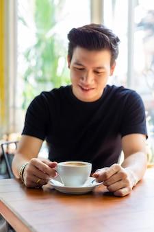 Junger mann, der heißen kaffee in der weißen schale schaut