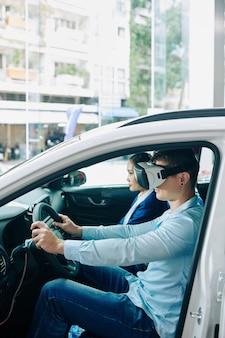 Junger mann, der helm der virtuellen realität trägt, wenn er auto für probefahrt nimmt