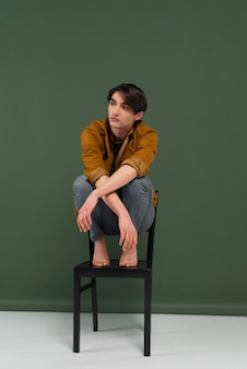 Junger mann, der hemd trägt, das auf stuhl aufwirft