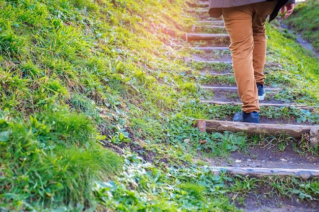 Junger mann, der herauf die treppe mit natürlichem hintergrund geht. schritt für erfolgskonzept.