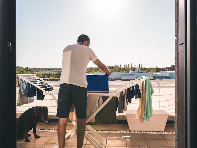 Junger mann, der heraus blaues t-shirt auf der terrasse seines dachbodens hängt. rückansicht