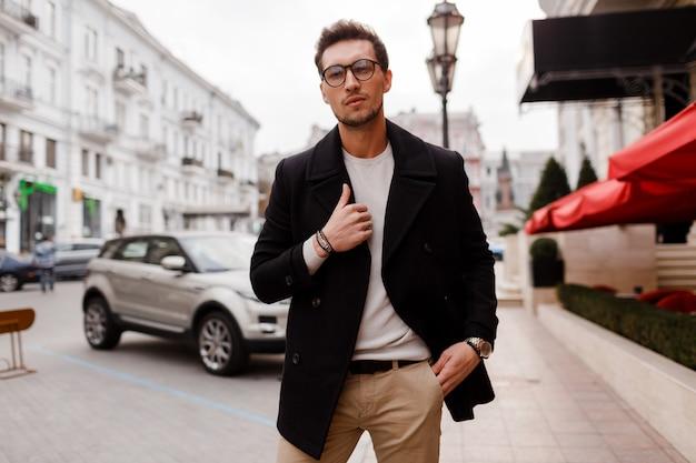 Junger mann, der herbstkleidung trägt, die auf der straße geht. stilvoller kerl mit moderner frisur in der städtischen straße.