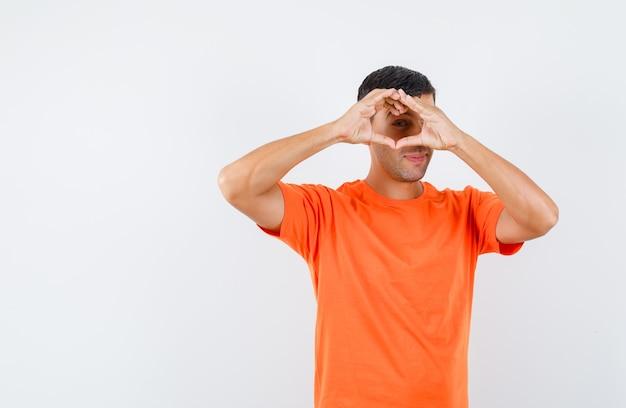 Junger mann, der herzgeste im orange t-shirt zeigt und lustig schaut