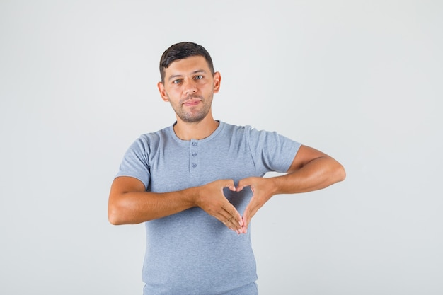 Junger mann, der herzgeste mit den fingern im grauen t-shirt macht