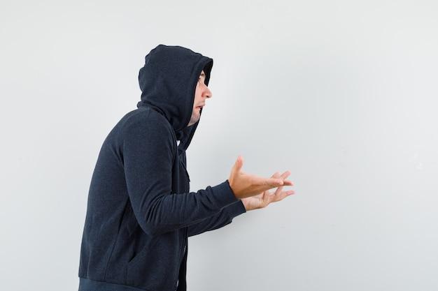 Junger mann, der hilflose geste im kapuzenpulli, im t-shirt zeigt und verwirrt schaut. .