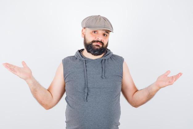 Junger mann, der hilflose geste in ärmellosem hoodie, mütze zeigt und verzweifelt aussieht. vorderansicht.