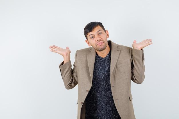 Junger mann, der hilflose geste in graubrauner jacke, schwarzem hemd zeigt und unentschlossen aussieht, vorderansicht.