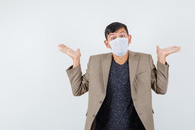 Junger mann, der hilflose geste in graubrauner jacke, weißer maske zeigt und verwirrt aussieht, vorderansicht.