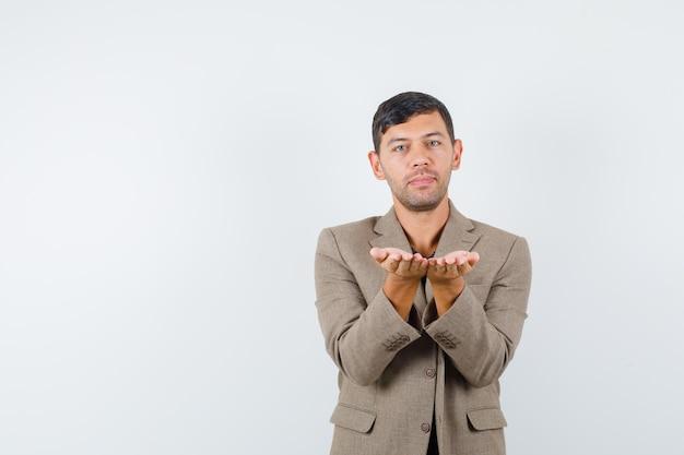 Junger mann, der hilflose geste in graubrauner jacke zeigt und ruhig aussieht, vorderansicht. freier platz für ihren text