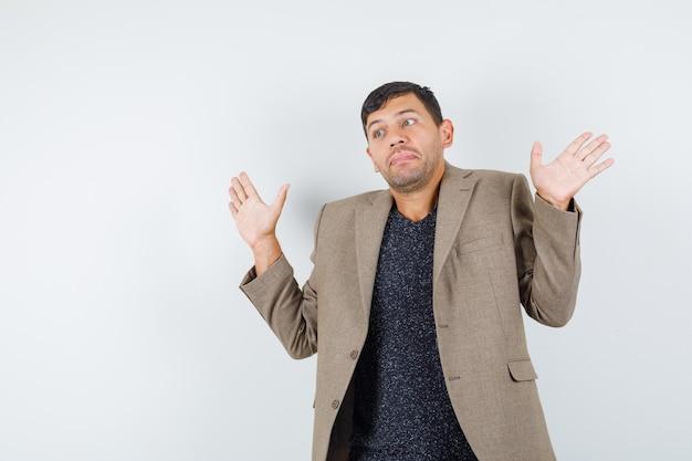 Junger mann, der hilflose geste in graubrauner jacke zeigt und verwirrt aussieht. vorderansicht.