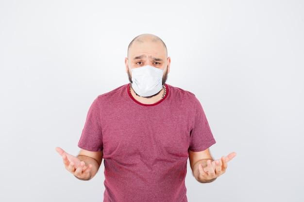 Junger mann, der hilflose geste in rosa t-shirt zeigt, vorderansicht der maske.