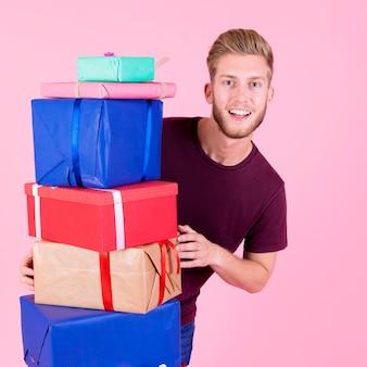 Junger mann, der hinter dem bunten stapel geschenken gegen rosa hintergrund steht