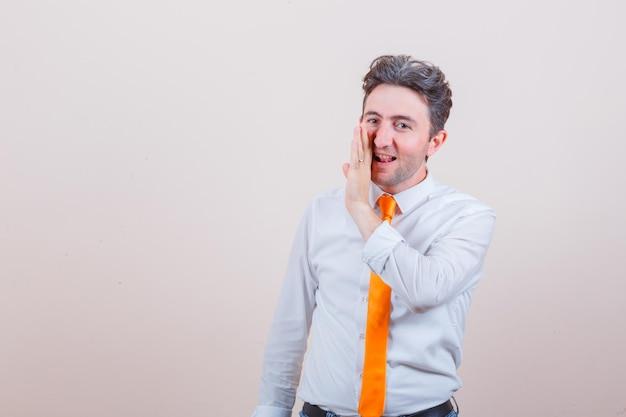 Junger mann, der hinter der hand im hemd ein geheimnis erzählt und neugierig aussieht